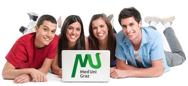 4 Studierenden liegen bäuchlings am Boden, lächeln in die Kamera und haben einen Laptop vor sich am Boden stehen.