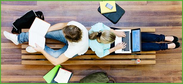 2 Studierende sitzen Rücken an Rücken und lernen